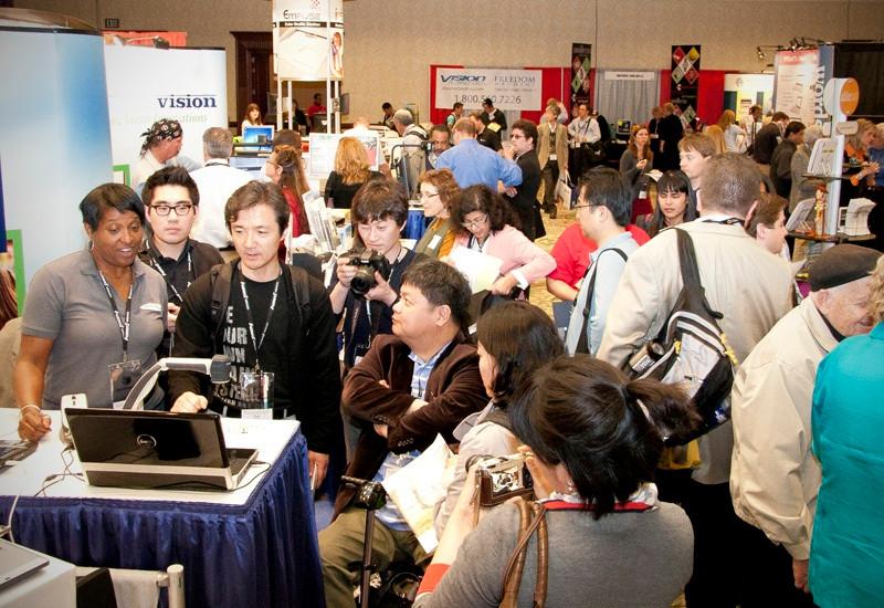 Bild från en tidigare konferens. En mängd människor står och tittar på en läskamera som präsenteras på en stånd på mässan.