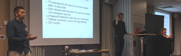 Foto som visar två män om föreläsar vid en storskärm. I bakgunden ses en teckenspråkstolk.