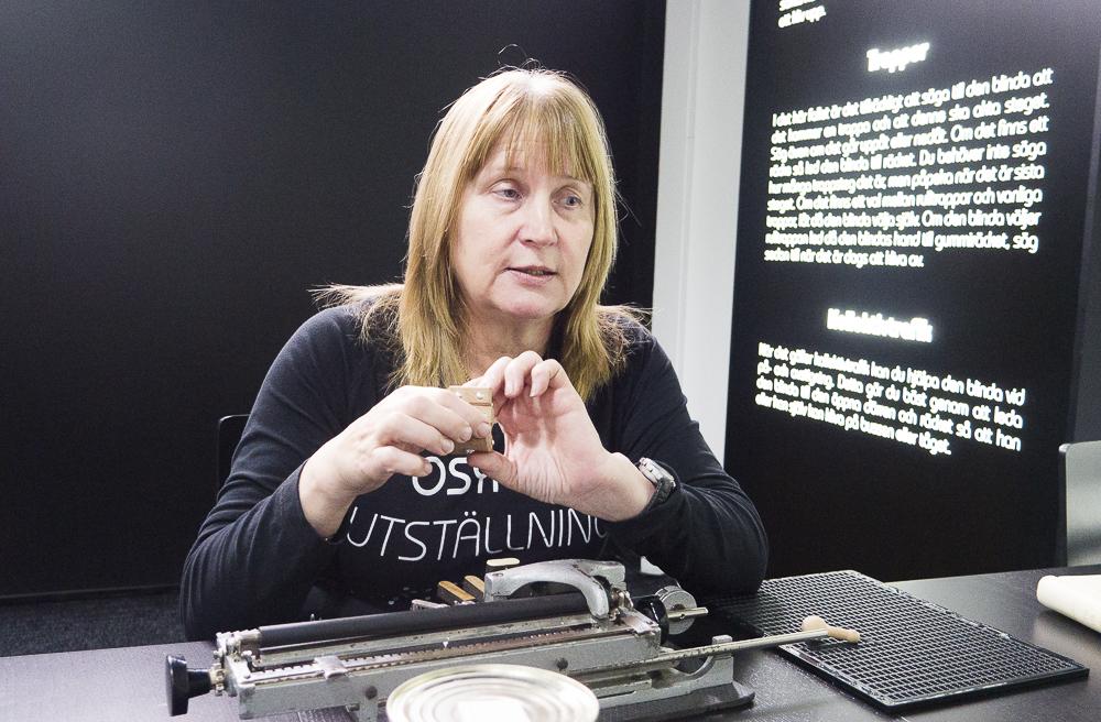 Sirkka Husso med halvlångt ljust hår och svart tröja framför en punktskriftsmaskin,