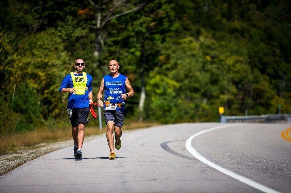 Britan Switzer springer på en landsväg tillsammans med en ledsagare.
