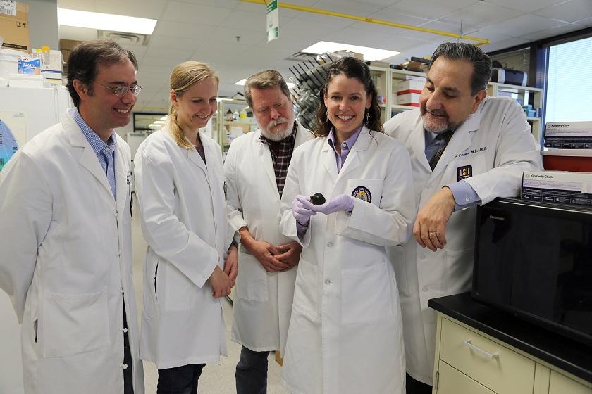 fem vitklädda forskare, i mitten Jennifer Lentz med usher-musen i handen.