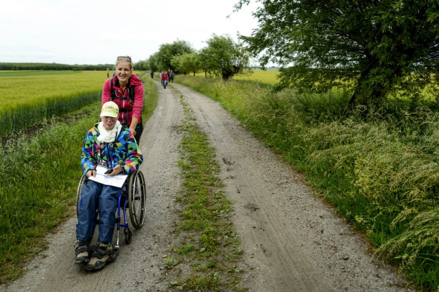 Christina i röd tröja bakom Tony som sitter i rullstol på en grusväg längs vandringsleden.