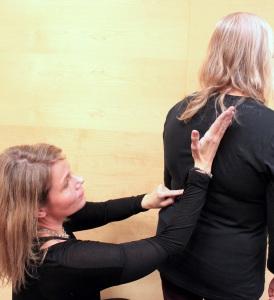 Pernilla Henriksson visar riktning på Linda Erikssons rygg