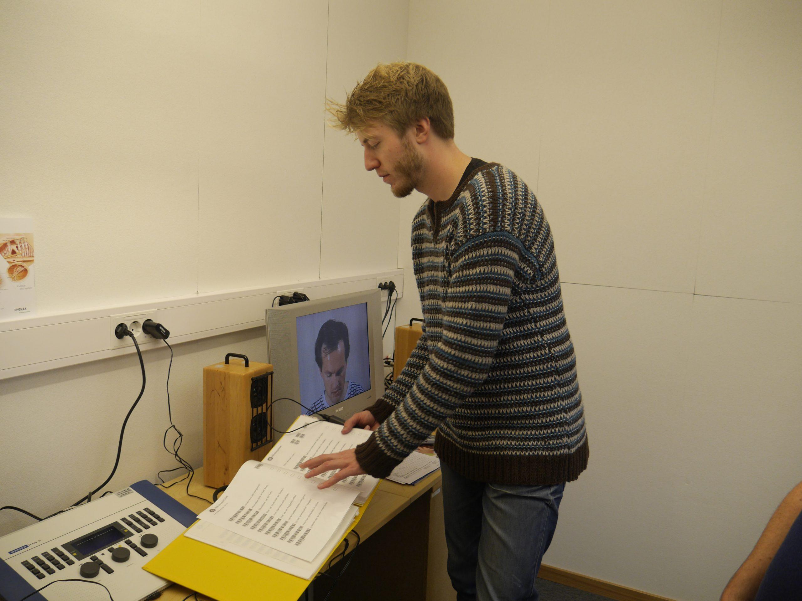 Audiolog Rolf Mjønes står framför en dator-