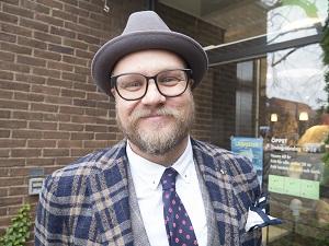 Porträtt Magnus Jarlövs i rutig kavaj och hatt.