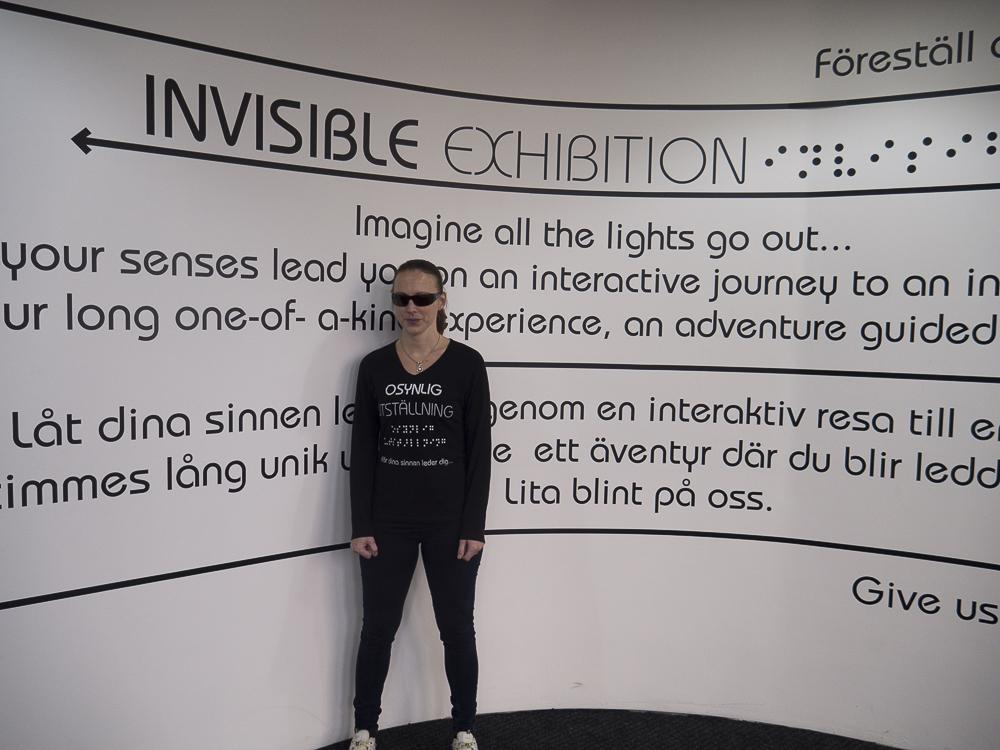 Annika Wistrand Elfving, svartklädd med solglasögon och håret i hästsvans framför utställningsbilden till Osynlig utställning
