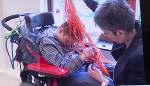 Erik i rullstol känner på tråddraperiet som hans partner håller över hans huvud