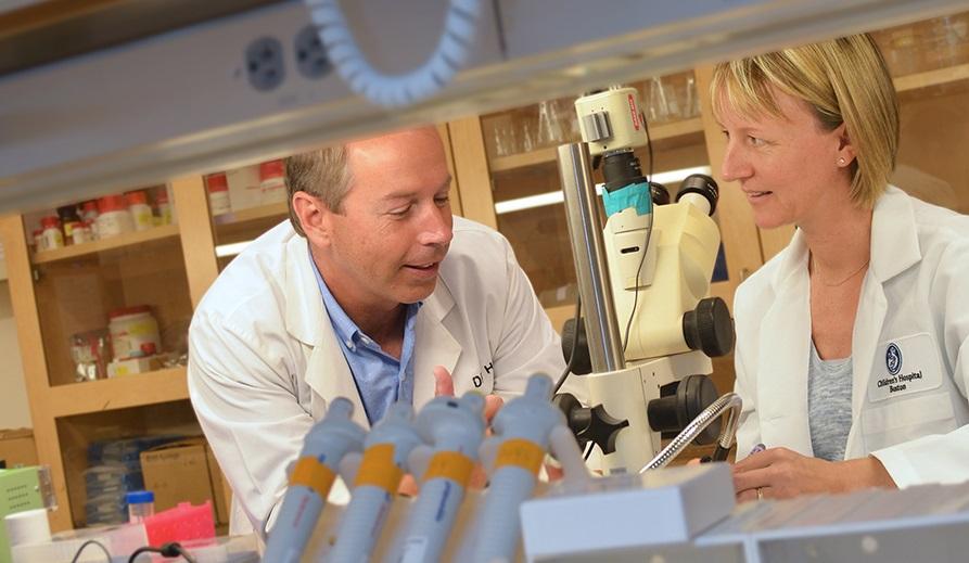 Forskarna i labbet, till vänster Jeffrey Holt, till höger Gwenaëlle S. Géléoc. Båda har vita rockar. I förgrunden syns provrör.