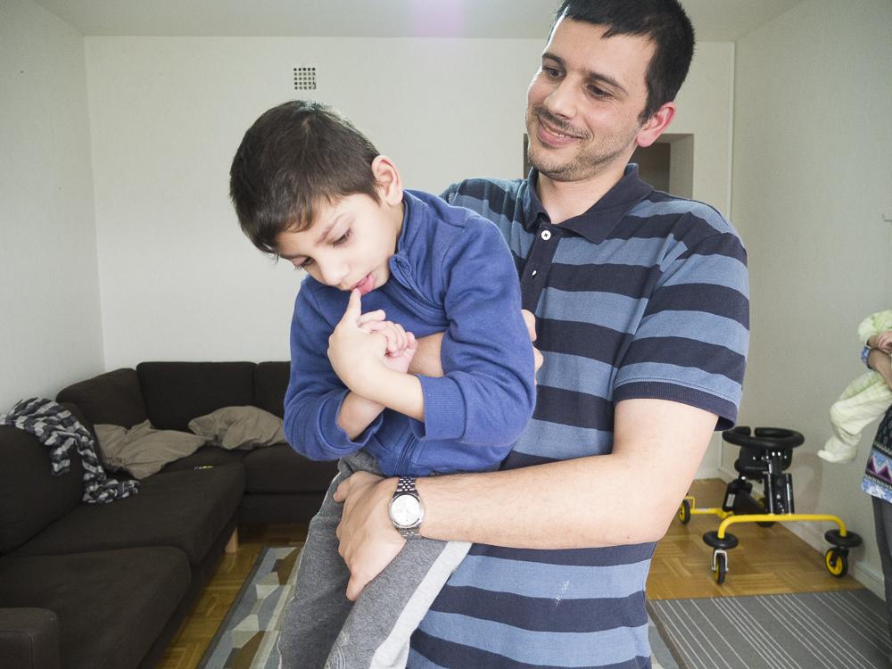 Pappa står upp och håller Ibrahim framför sig,