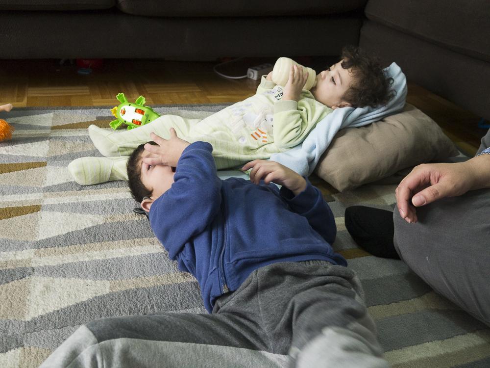 Bröderna ligger på den stora mattan i vardagsrummet.
