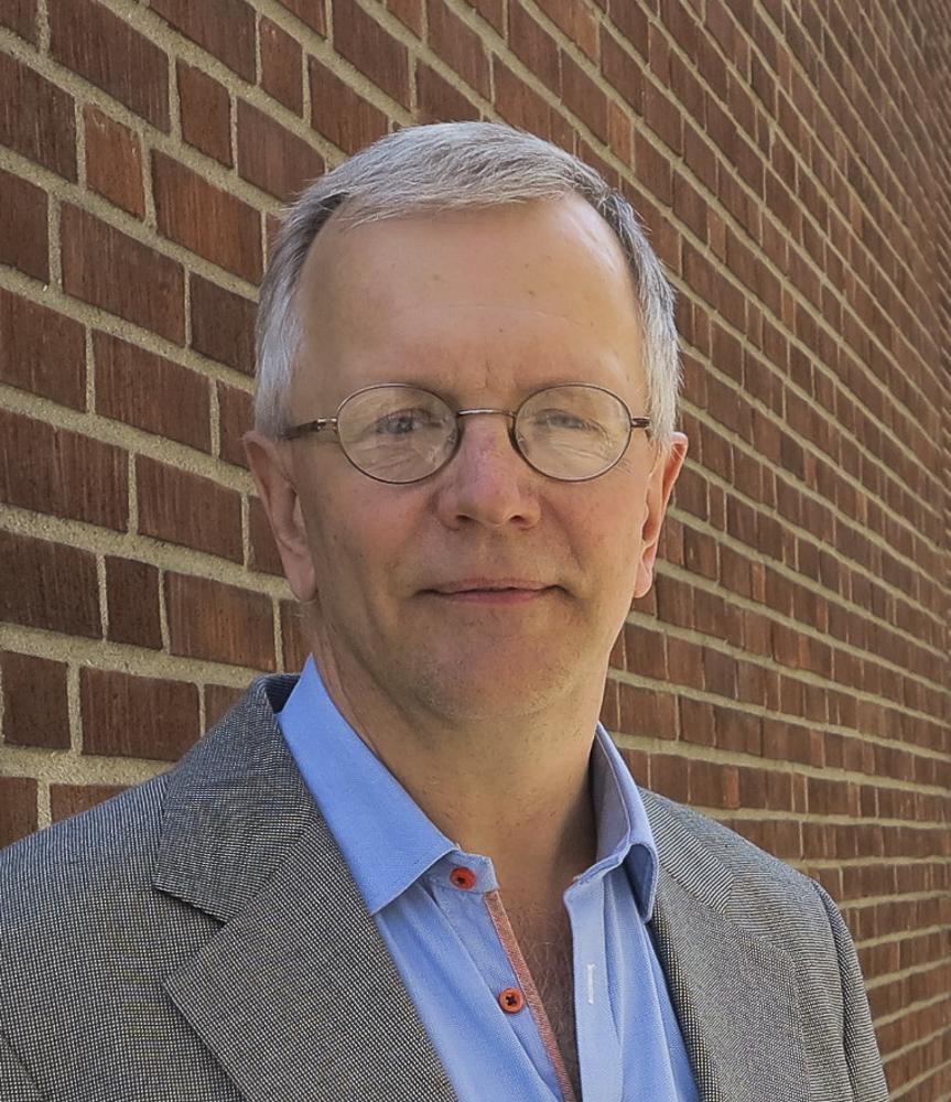Anders med grått hår och glasögon står vid en tegelvägg. Blå skjorta med röda knappar och kavaj,