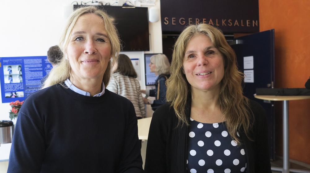 Ann-Charlotte till vänster har mörk tröja och ljust hår i svans, Sara till höger har halvlångt cendréfärgat hår och blommig klänning.
