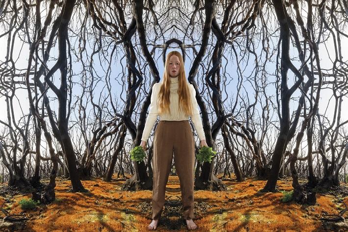 En kvinna i långbyxor står i en skog.