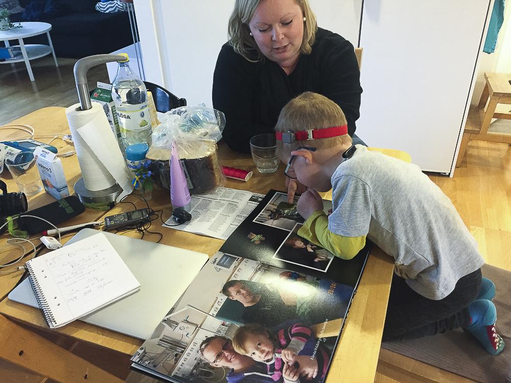Moltas hemma vid köksbordet på knä på en stol och med näsan i boken om sig själv. I bakgrunden mamma Emelie.