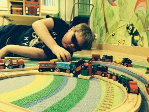 Hugo med ljust hår och mörka glasögon, ligger på golvet och leker med en tångbana som går över en färggrann matta i gult och grönt.