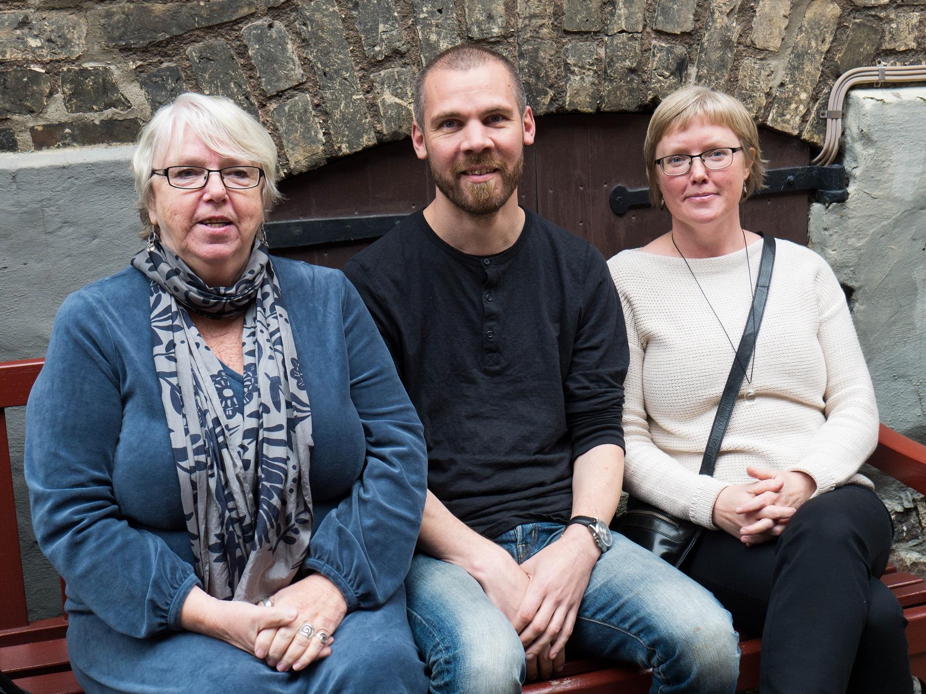 Från vänster sitter Birgitta Lööv, Hugos mormor i vitt kort hår, gasögon och en blå kläning. I mitten pappa Olle med kort skgg, svart tröja och jeans och till höger Malin med ljus tröja. De sitter utomhus på en bänk.