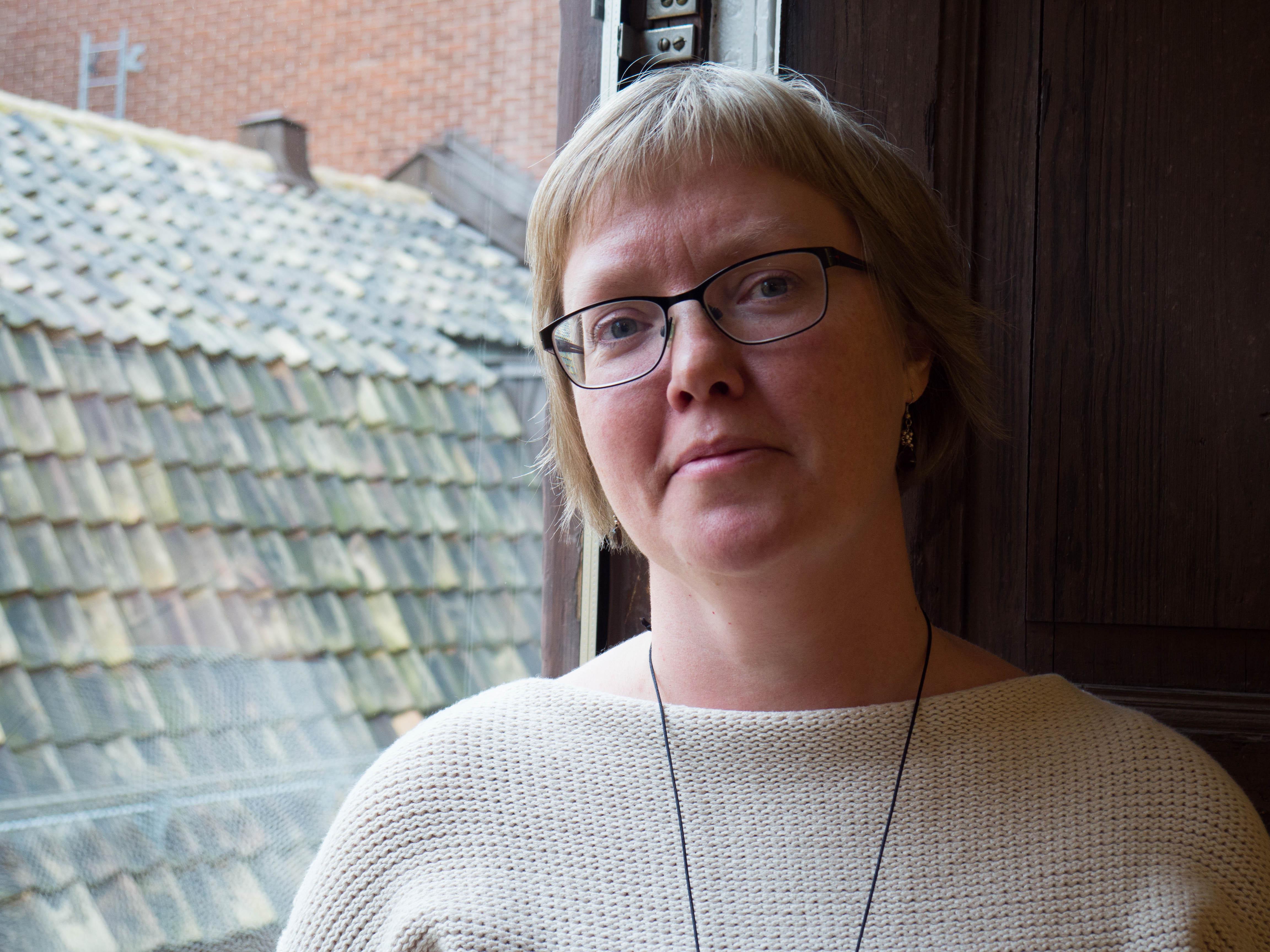Malin Asplund, kortklippt med glasögon och ljust beige tröja står i ett fönster