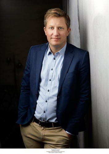 Mattias i blå blaxwer och ljusblå skjorta lutar sig mot en vägg med händerna i byxfickorna