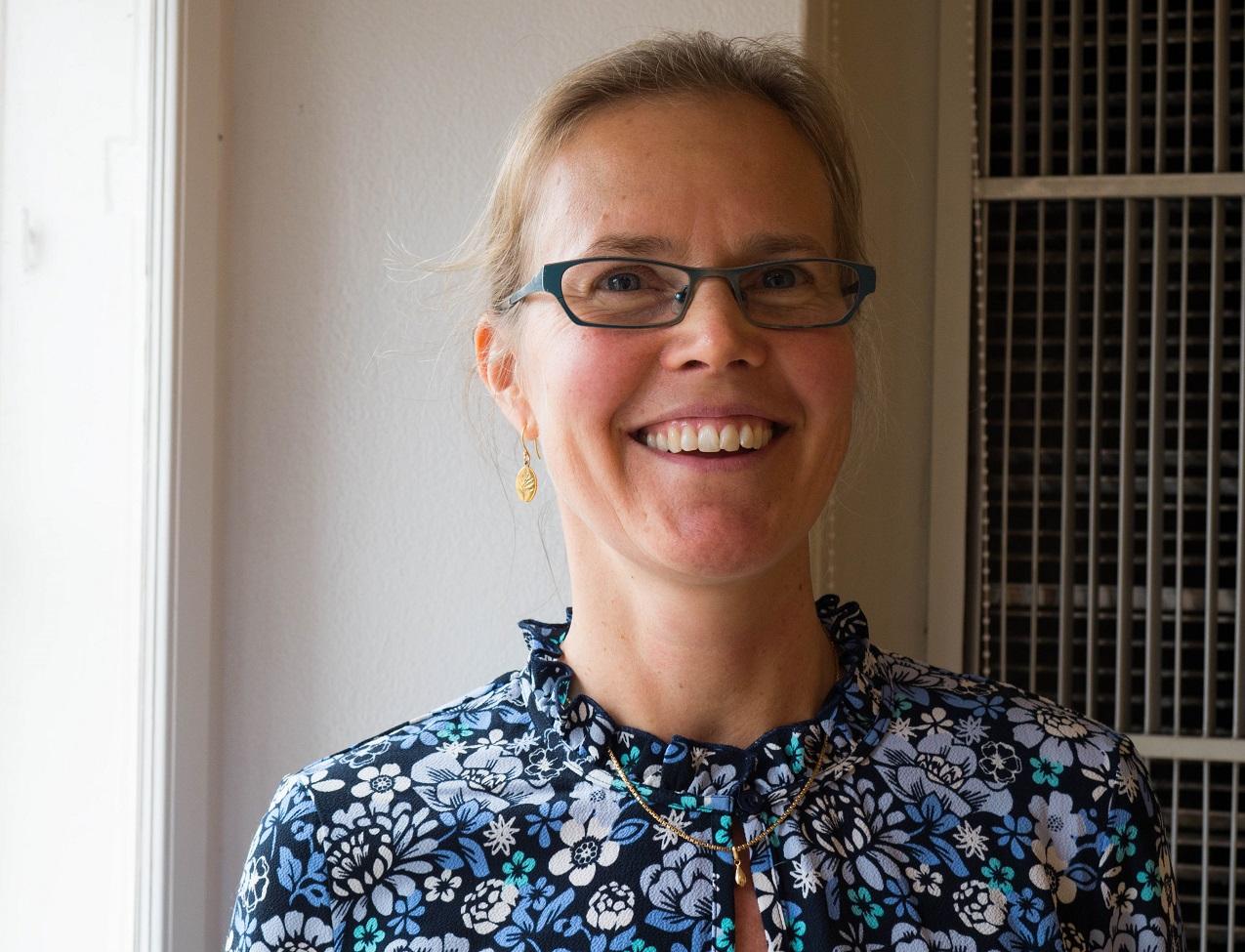 Porträtt Ulrika Kjellström som har ljust bakåtkammat hår, blåblommig blus, blå glasögon och ler.