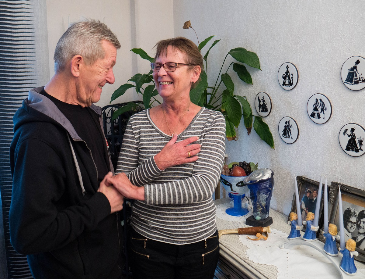 Hans och Eva står upp i vardagsrummet,. Hans håller Eva i handen. De ler mot varandra, Till höger på väggen hänger tallrikar som Eva målat.