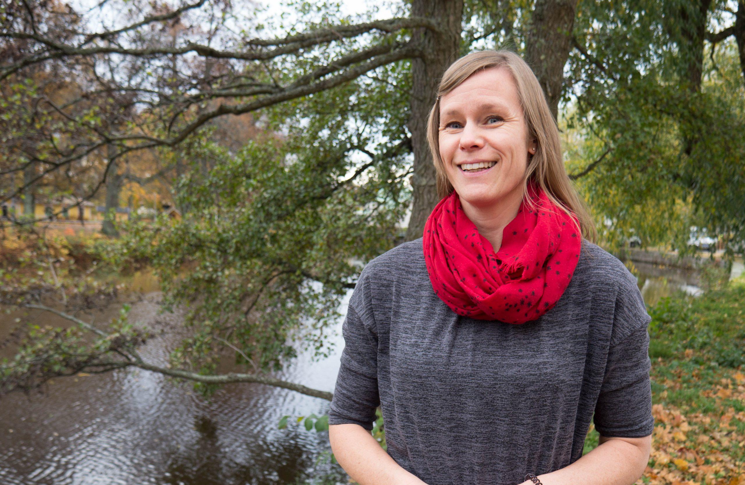 Elin i ljust långt hår, grå klänning och röd sjal står i en park intill en flod.