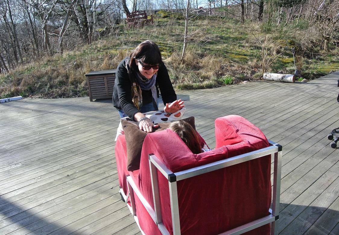 Bilden tagen bakifrån på det stora trädäcket. anne-Marie trummar på kudden som ligger i Anjas knä.