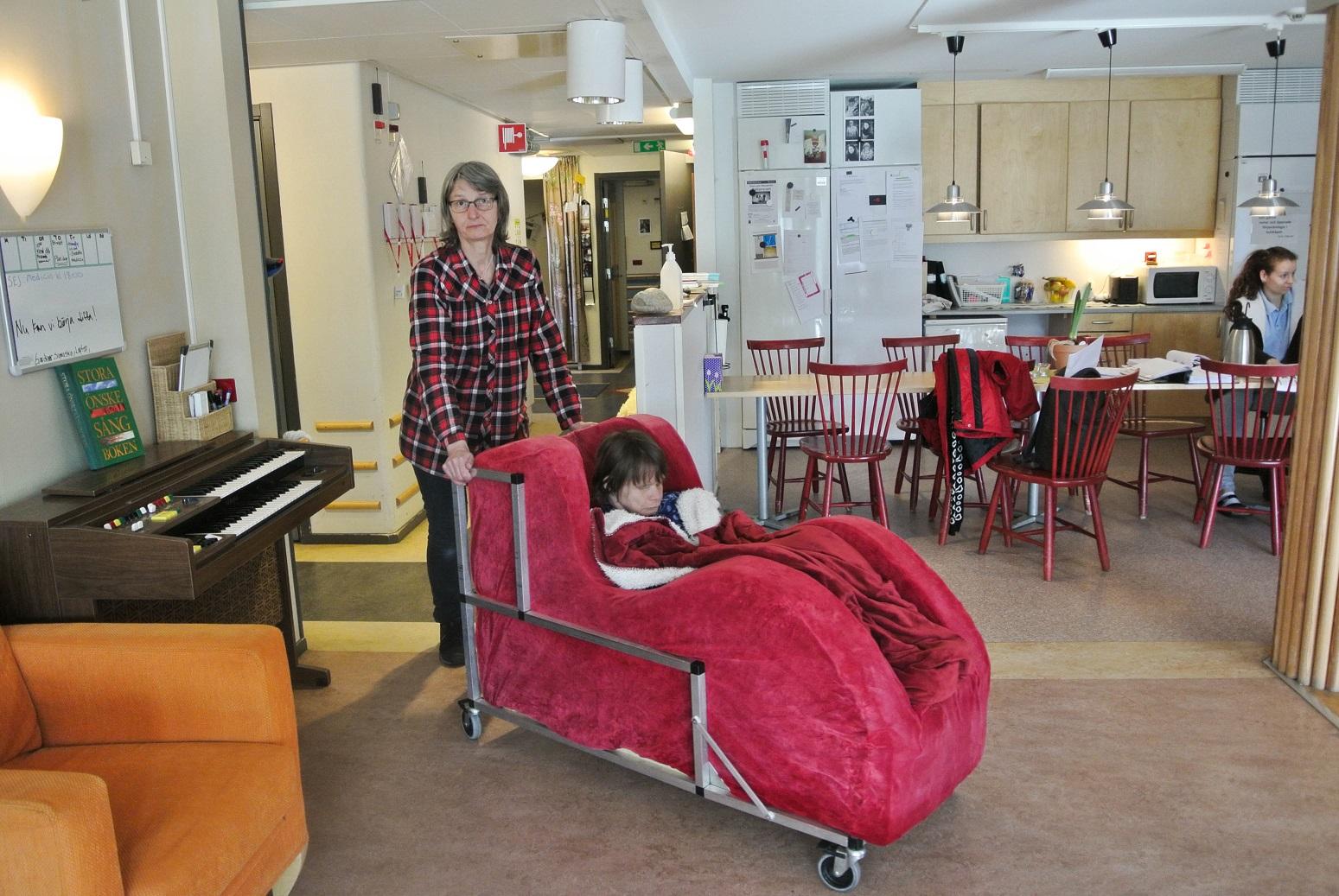 Ulla i kort ljust hår och rutig skjorta kör Anja som sitter i den röda stolen med en filt poå sig. I bakgrunden syns köksbordet med stolar.