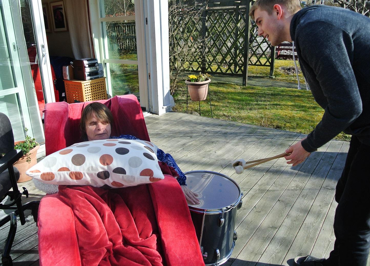 Anja halvligger i den röda stolen med en prickig kudda på magen. Ena handen är på trumman till vänster. John står intill och trummar.