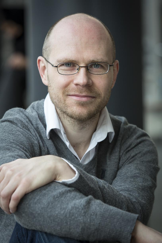 porträtt av Jesper i grå tröja med ljus skjorta. Jesper är snabbad, har glasögon och mycket kort skägg. an