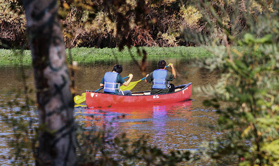 Tvpå personer i blåa flytvälstar paddlar i en röd kanot,
