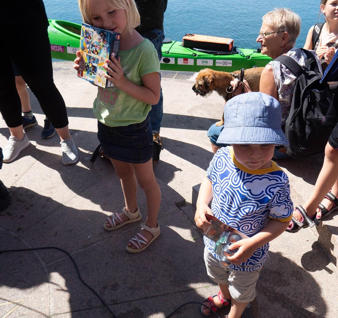 Alva med ljust hår, grön tröja och shorts med ett legopaket i handen. till höger Hugro i blå solhatt.