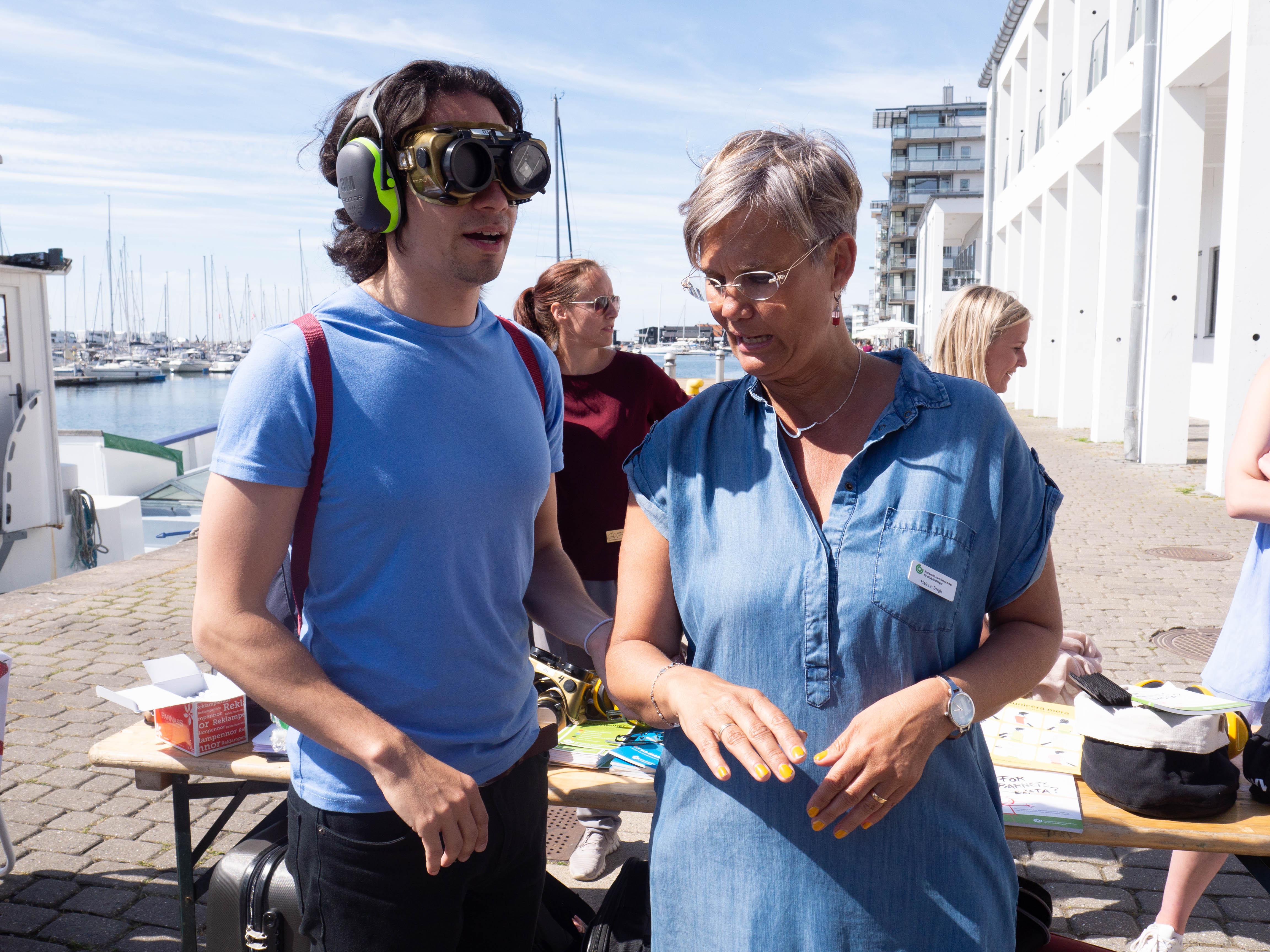 Kille med fingerad optik och ljusblå t-shirt till vänster, ledsagas av Helene i ljusblå sommarklänning.