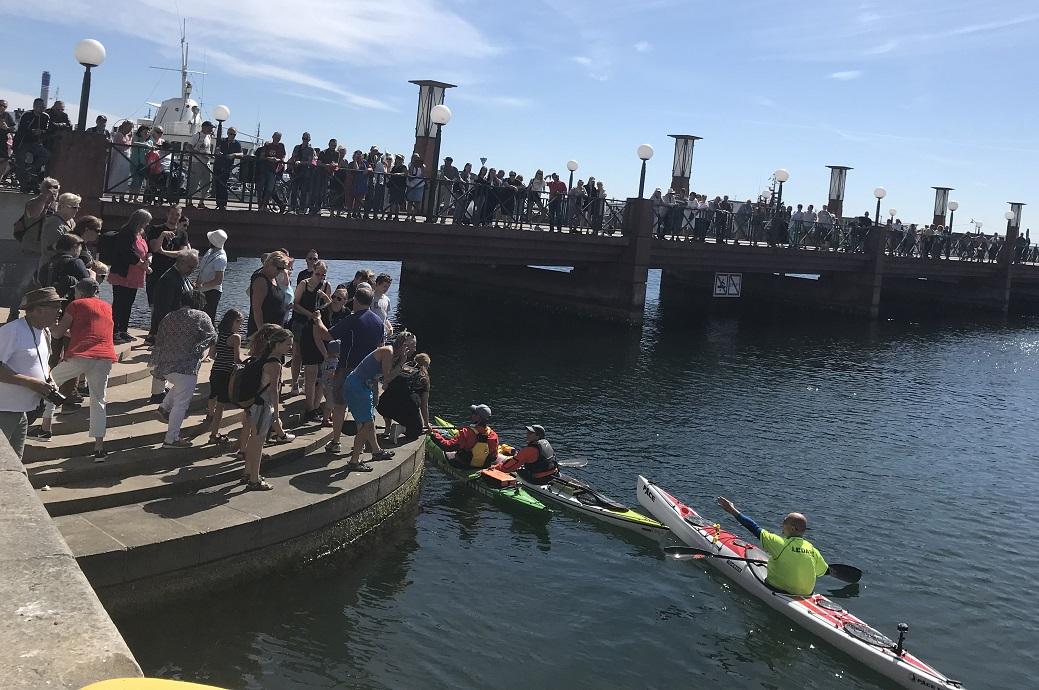 Torbjörn tas emot på bryggan. Efter kommer Leif Davissons kanot. Mycket folk på bryggan, händer sträcks ut.