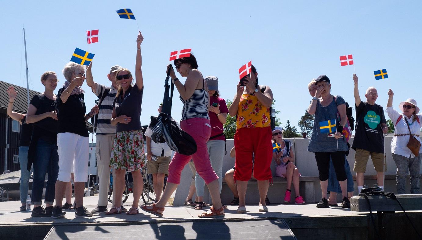 Danskar med både svenska och danska flaggor står på kajen och viftar när kajakerna lämnar Helsingör