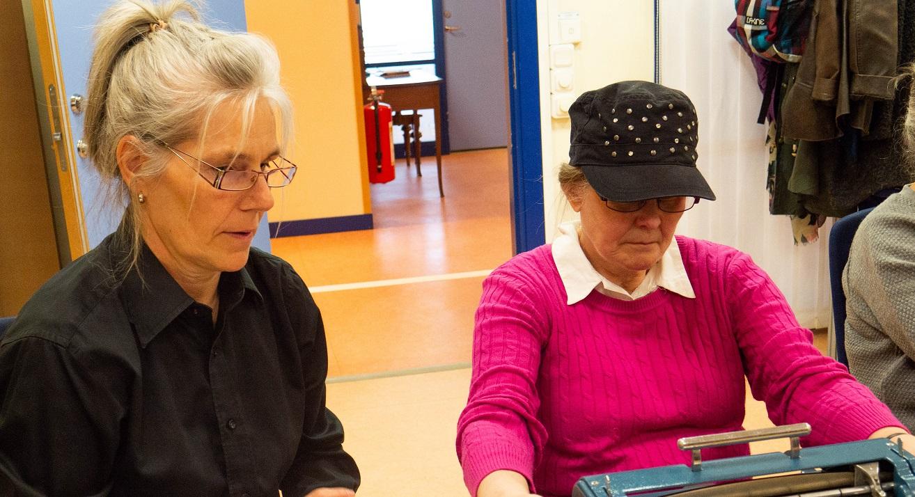 Catarina i svart skjorta, glasögon och det ljusa håret i hästsvans till vänster. Christina i svart keps och knallrosa tröja vid maskinen.