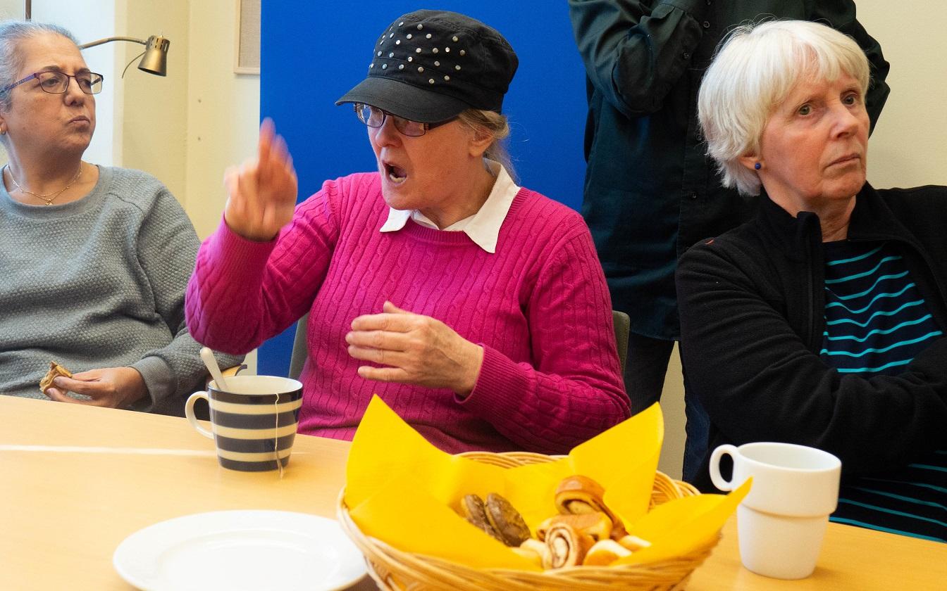 Malin i grå tröja och glasögon lyssnar när Chrstina tecknar. Britt-Marie längst till höger. Framför dem ett fat med bullar.
