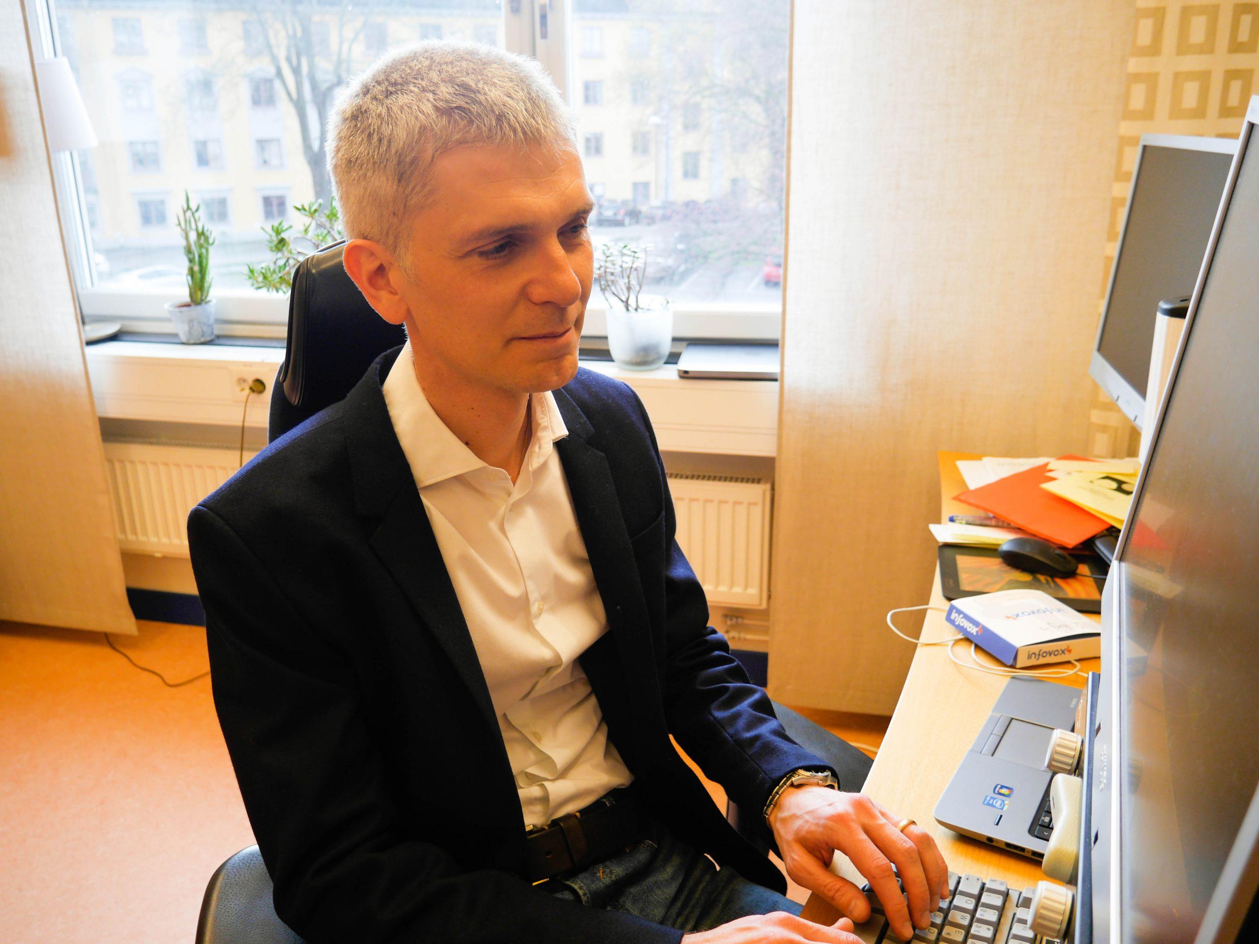 Mattias sitter vid datorn i mörkblå kavaj och ljus skjorta.