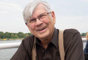 Porträtt på Bill som har grått hår, glasögon, brun skjorta och beige hängslen