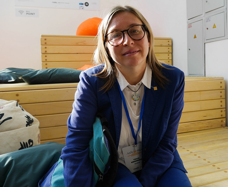 Julia i glasögon, ljust halvlångt hår. blå kavaj och vit skjorta sitter på en träbänk