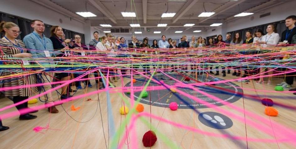 många människor står i en halvcirkel, fokus är på garnerna i olika självlysande färger som bildar ett nät