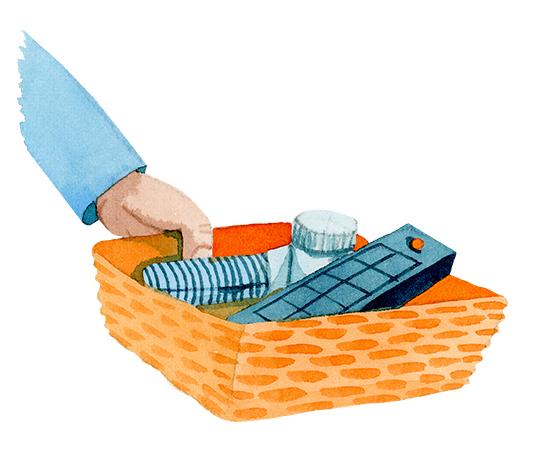 En hand håller en korg som innehåller fjärrkontroll och medicinburk