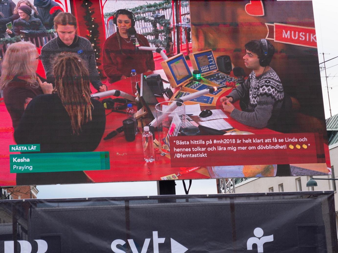 Till vänster står Linda i buren. Intill henne, med ryggen mot kameran står tolken Sra, till vänster token Julia, Farah med flätor tittar på och William som sitter bakom skrivbordet. framför ett antal skärmar och reglage och med hörlurar på sig.