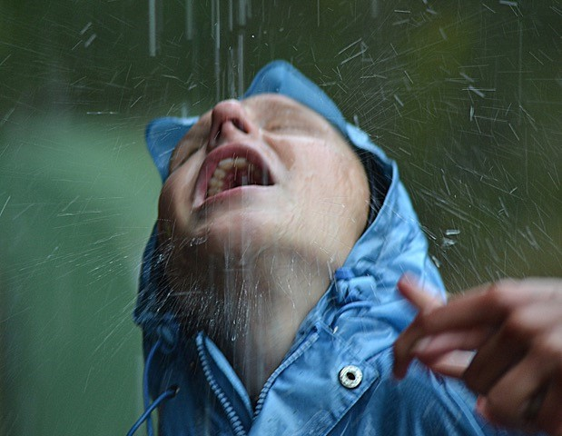 Det regnar. Tormod i blå regnjacka lyfter ansiktet mot regnet.