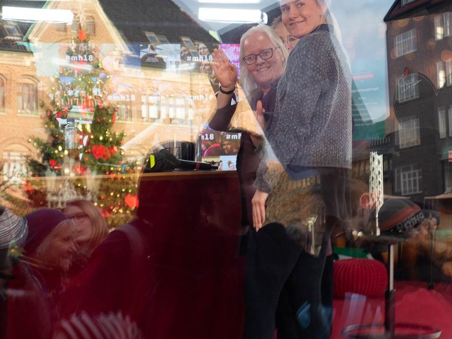 Linda och tolken Julia skymtar på bilden. Den är tagen utiifrån, och i glasrutan ser man granen på torget och husen vid sidan av.