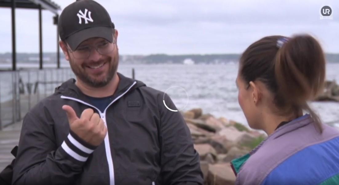 Torbjörn till högeri keps och grå tröja sitter vid havet,. ITill höger ses reportern med mörkt hår och hästsvans, bakifrån.
