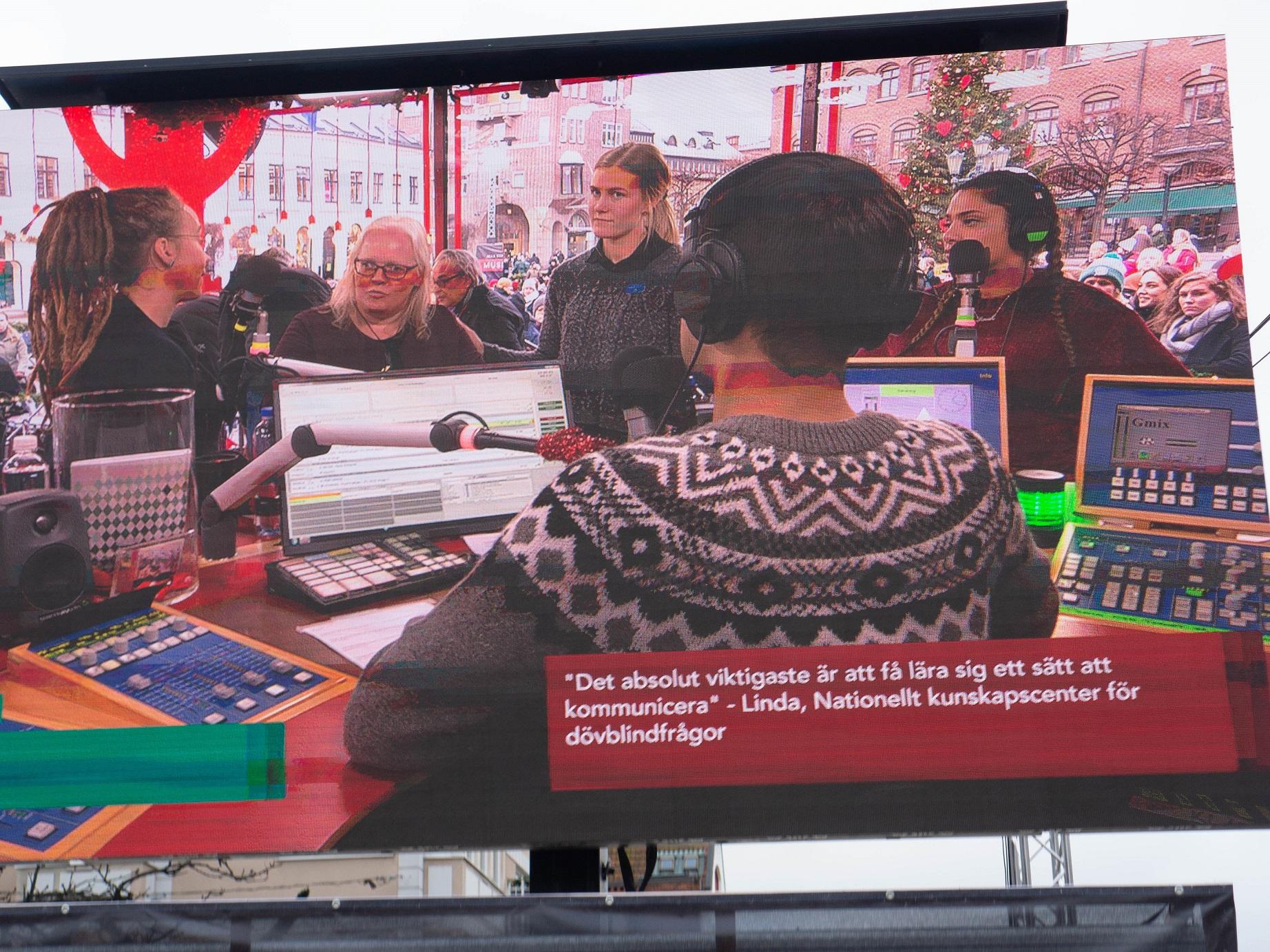 William i gråsvartvit islandströja ses bakifrpn. Till höger i bild Fara och rakt fram Linda omgiven av tolkarna Sara, till vänster och Julia till höger. Genom fönstret syns julgranen på Stortorget