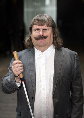 Håkan Thomson i grå kostym, långt hår och mustasch. Teknikkäpp i höger hand