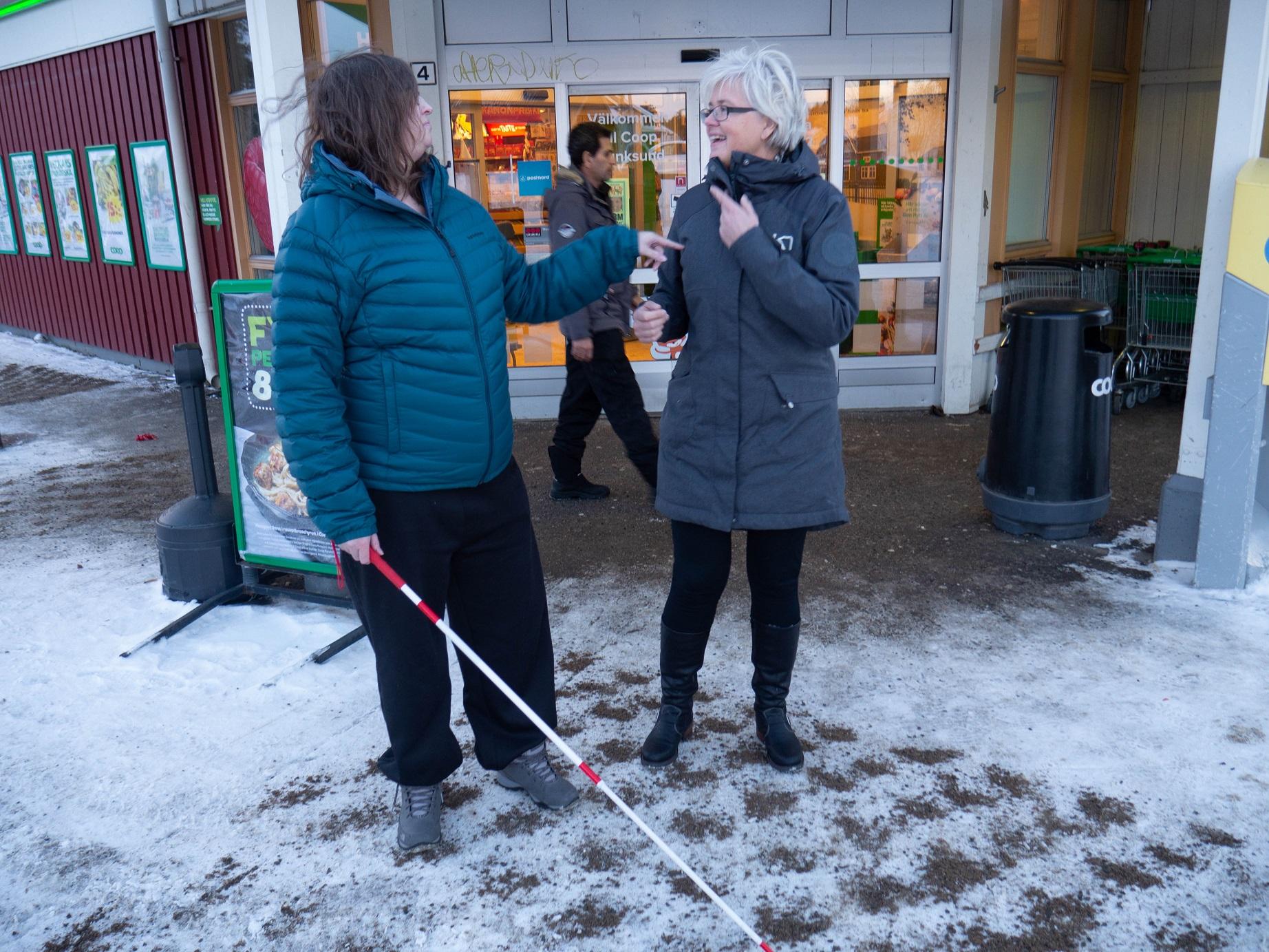 Evelina i blå täckjacka och rödvitrandig teknikäpp till vänster och mamma Ingela i blågrå kappa till höger står utanför affären. På marken snö.