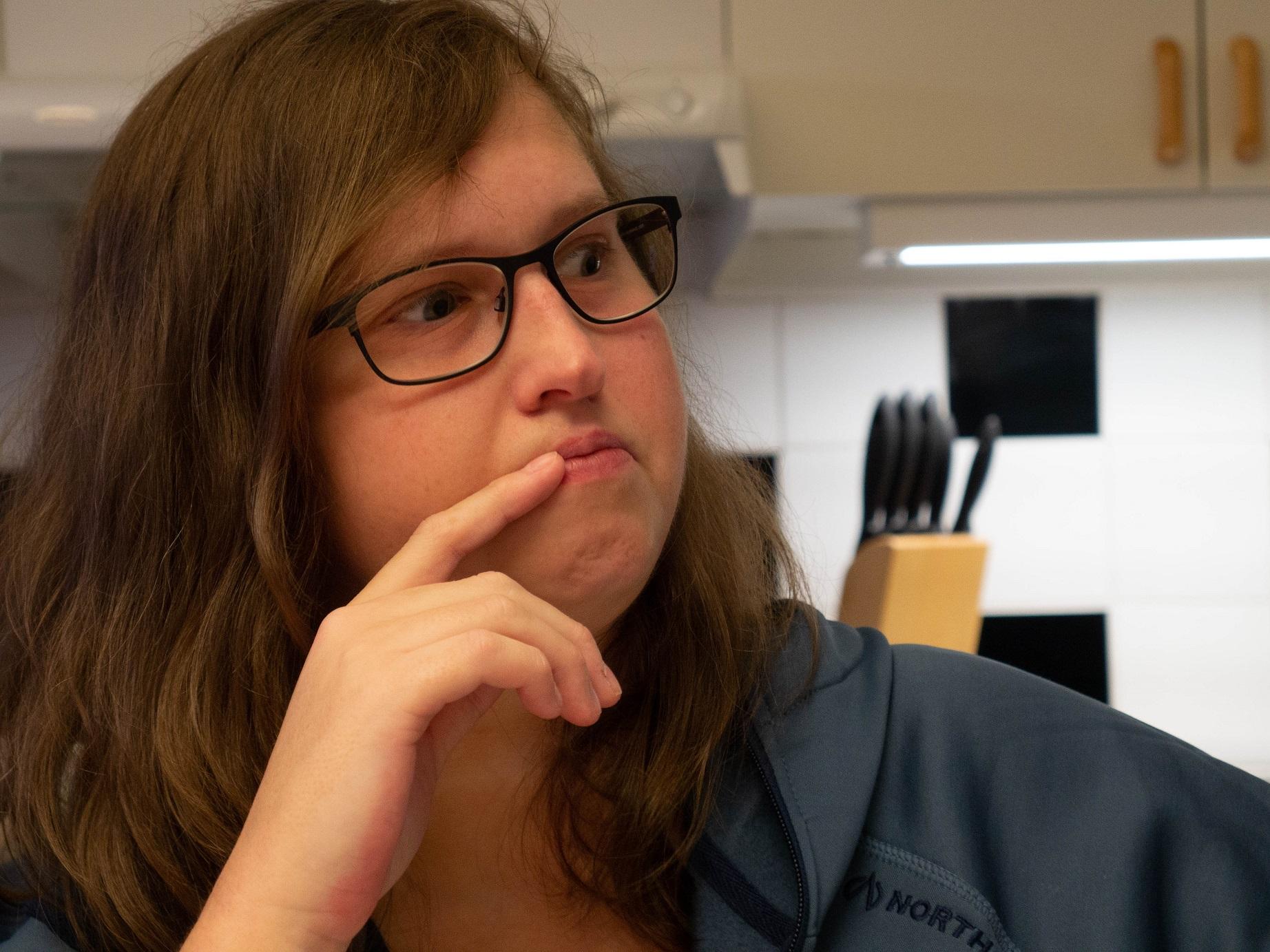 Porträtt. Evelinai brunt halvlångt hår och glasögon tittar åt vänster med fingret mot läppen.