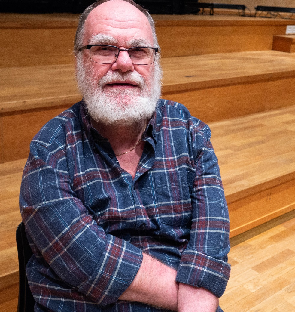Lars i glasögon och vitt skägg, i blå och rödrutig skjora.